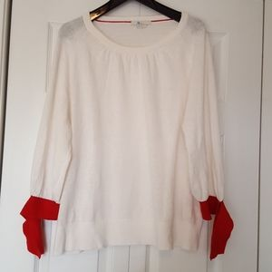 Biden cream and red sweater with ties at sleeve